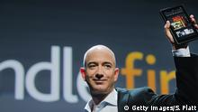 NEW YORK, NY - SEPTEMBER 28: Amazon founder Jeff Bezos holds the new Amazon tablet called the Kindle Fire on September 28, 2011 in New York City. The Fire, which will be priced at $199, is an expanded version of the company's Kindle e-reader that has 8GB of storage and WiFi. The Fire gives users access to streaming video, as well as e-books, apps and music, and has a Web browser. In addition to the Fire, Bezos introduced four new Kindles including a Kindle touch model. (Photo by Spencer Platt/Getty Images)