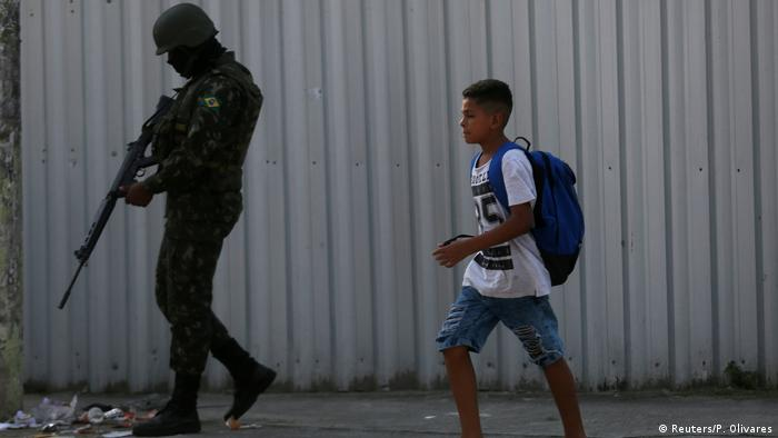 Boy walking past soldier in Rio de Janeiro