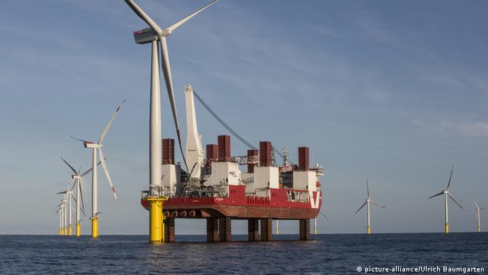 Wind turbines and a turbine installation ship (picture-alliance/Ulrich Baumgarten)