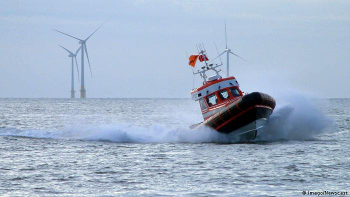 Photo of a sea rescue boat with offshore wind turbines in the background.