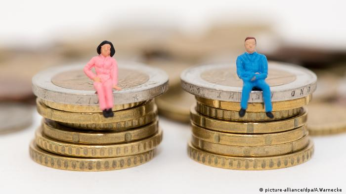 A man and a woman sitting on stacked coins