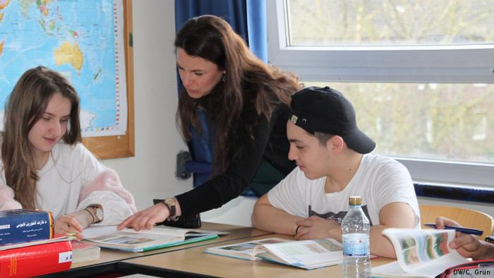 A teacher works with two students in a classroom (DW/C. Grün)