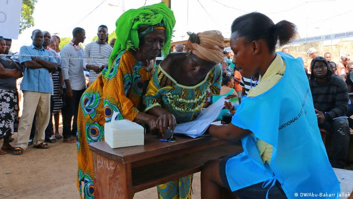 Two women at the ballot box, watched by an election official (DW: Abu-Bakarr Jalloh)