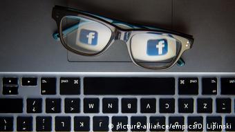 На компьютере лежат очки, на стеклах которых изображен логотип Facebook