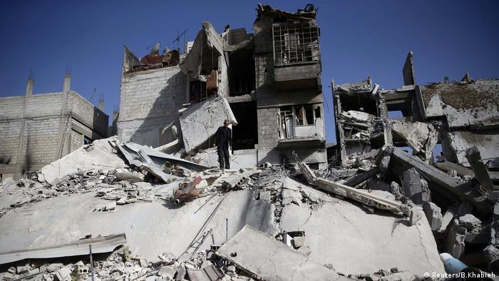 Homem observa uma construção destruída em Duma, cidade de Ghouta Oriental (5 de março de 2018)