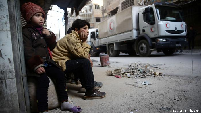 A boy and a girl sit down in the rebel enclave of east Ghouta (Reuters/B. Khabieh)