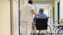 ARCHIV - Eine Krankenschwester steht am 01.07.2015 im Universitätsklinikum Carl Gustav Carus in Dresden (Sachsen) neben einem Patienten im Rollstuhl vor einem Behandlungszimmer. (zu dpa Krankenkassen pochen auf Gesamtkonzept für Pflege im Krankenhaus am 11.01.2018) Foto: Sebastian Kahnert/dpa-Zentralbild/dpa +++(c) dpa - Bildfunk+++ | Verwendung weltweit