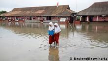 Students walk in the yard of the Pantai Bahagia Elementary School, inundated with sea water after the tide came in, in Bekasi, West Java province, Indonesia, February 1, 2018. REUTERS/Darren Whiteside SEARCH COASTLINE INDONESIA FOR THIS STORY. SEARCH WIDER IMAGE FOR ALL STORIES.