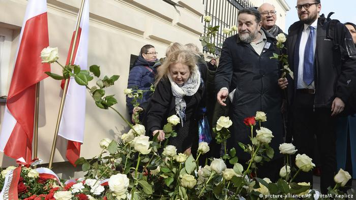 People lay flowers at a ceremony to commemorate 50 years after student protests and an anti-Semitic purge in Poland (picture-alliance/AP Photo/A. Keplicz)