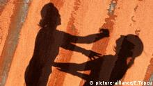 Shadows of a woman punching another woman fall on a wall (picture-alliance/E.Topcu)