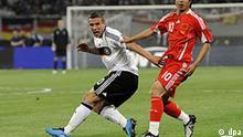 Fußball, Länderspiel, China - Deutschland, am Freitag (29.05.2009) im Shanghai Stadium in Shanghai in China. Deutschlands Lukas Podolski (l) und Chinas Hao Junmin kämpfen um den Ball. Foto: Marcus Brandt dpa +++(c) dpa -
