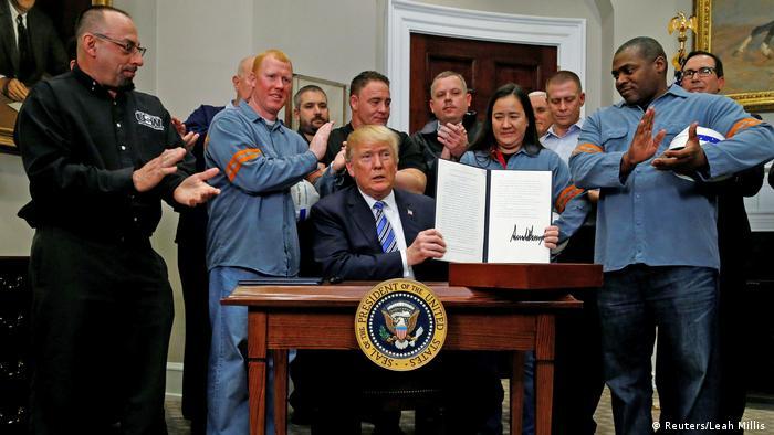El presidente Donald Trump en la Oficina Oval rodeado de trabajadores del acero.