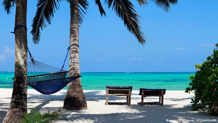 Tropical beach in Zanzibar with palm trees, hammock and canvas chairs (picture alliance / blickwinkel/M)