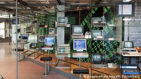 Ein Raum im Heinz Nixdorf MuseumsForm HNF: mehrere Computer aus verschiedenen Jahrzehnten stehen auf Metallstäben und schmalen Tischen. Davor jeweils eine Sitzgelegenheit. Im Hintergrund eine Ausstellungsvitrine