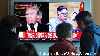 Trump and Kim Jong Un appear side by side on a TV screen with Korean text as people look on (picture-alliance/AP Photo/A. Young-joon)