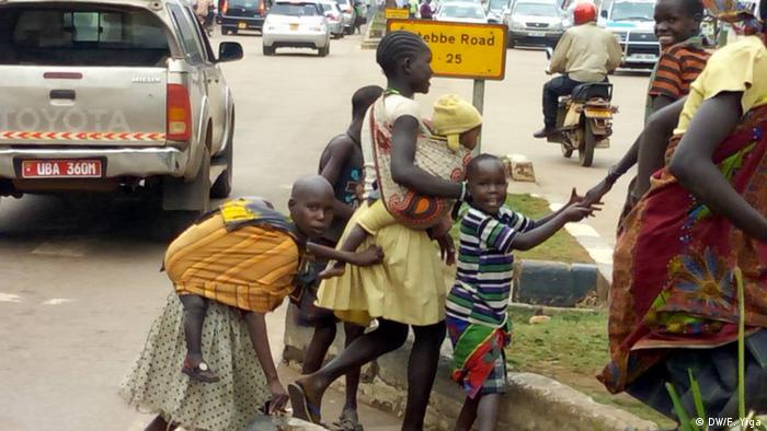 Street kids carrying toddlers cross a street in Kampala (DW/F. Yiga)