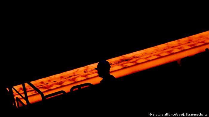 A profile shaded against a red-hot steel girder (picture alliance/dpa/J. Stratenschulte)