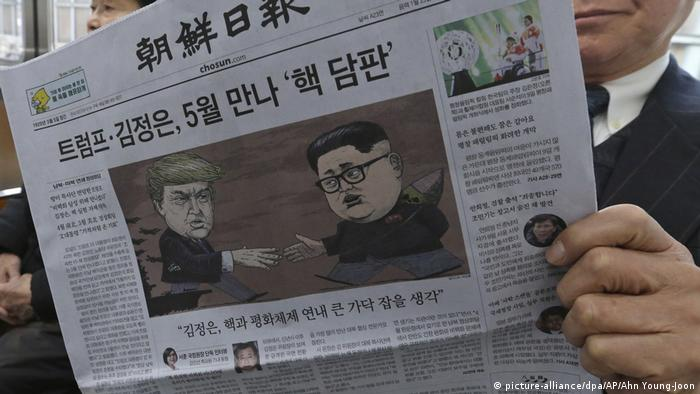 A South Korean man reads newspaper with Kim and Trump's caricatures