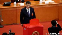 Chinese President Xi Jinping looks on after dropping his ballot during a vote on a constitutional amendment lifting presidential term limits