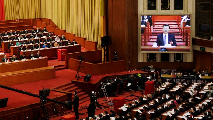 Chinese president Xi Jinping is seen on a giant screen during a plenary session of the National People's Congress at the Great Hall of the People in Beijing