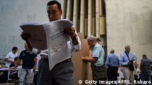 11.03.2018 A man looks at an electoral sheet before marking his vote at a polling station in Cali, Valle del Cauca Department, during parliamentary elections in Colombia on March 11, 2018. Colombians went to the polls Sunday to elect a new Congress with a resurgent right, bitterly opposed to a peace deal that allows leftist former rebels to participate, expected to poll strongly. The election is set to be the calmest in half a century of conflict in Colombia, with the former rebel movement FARC spurning jungle warfare for politics, and the ELN -- the country's last active rebel group -- observing a ceasefire. / AFP PHOTO / Luis ROBAYO (Photo credit should read LUIS ROBAYO/AFP/Getty Images)