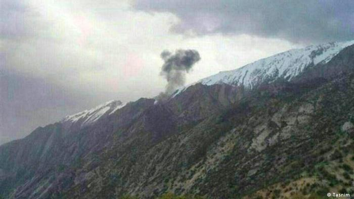 Smoke from a Turkish jet rises from its wreckage on a mountainside