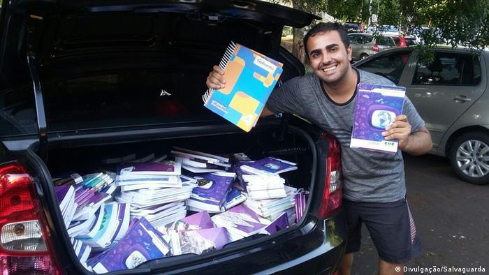 Vinícius de Andrade, fundador do Salvaguarda, mostra o porta-malas de um carro cheio de apostilas para ajudar estudantes da rede pública
