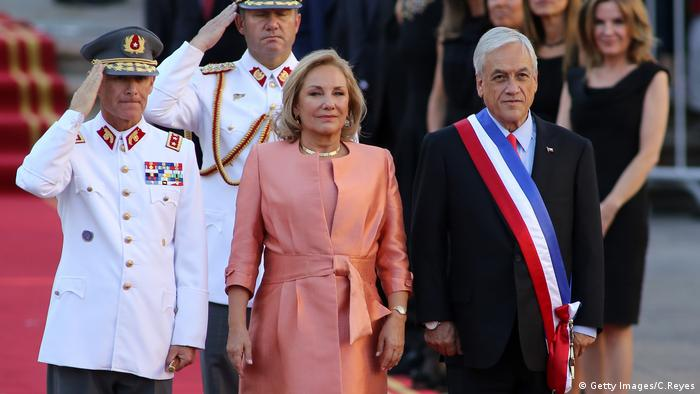 Chilean President Sebastian Pinera (R) and his wife Cecilia Morel stand upon arrival at La Moneda presidential palace in Santiago