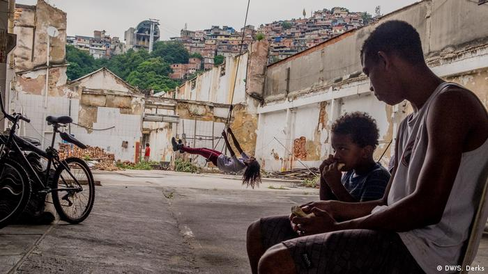 A man and a boy sitting next to each other in the harbor area Mariana Crioula, (DW/S. Derks)
