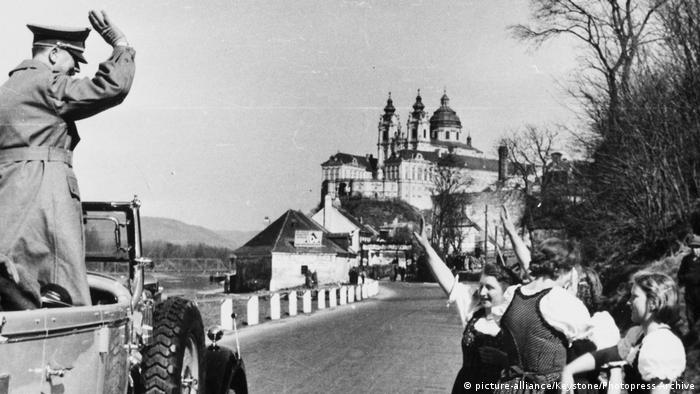 Hitler and young women in dirndls exhange Nazi salutes with the Melk monastery in the background