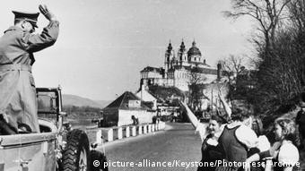Adolf Hitler is greeted by Austrians showing the Hitler salute