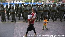 A Chinese Uighur woman walk past a line of soldiers in Urumqi, Xinjiang province (picture-alliance/dpa/epa/D. Azubel)