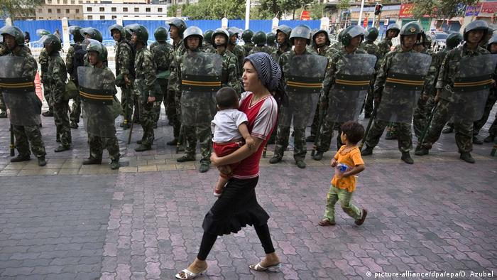 An ethnic Uighur woman carrying a baby and with a younger girl walk pass a line of soldiers patrolling a Uighur neighborhood