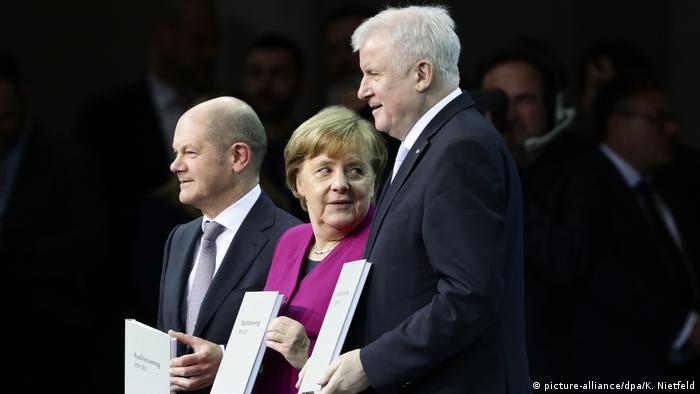 German Chancellor Angela Merkel next to Horst Seehofer and Olaf Scholz