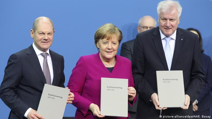 Three German politicians hold up copies of the coalition agreement
