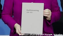 Angela Merkel poses with the coalition agreement during a signing ceremony in Berlin, Germany