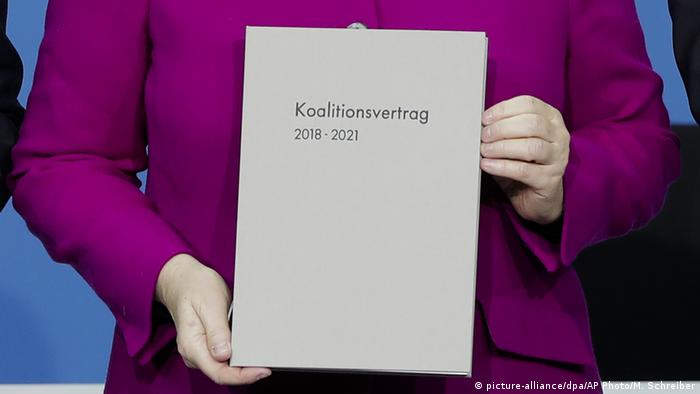 Merkel holding a copy of the current governing coalition agreement (picture-alliance/dpa/AP Photo/M. Schreiber)