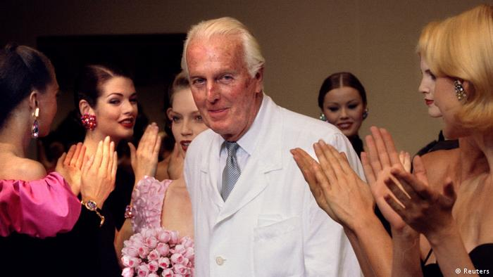 French fashion designer Hubert de Givenchy is applauded by the models