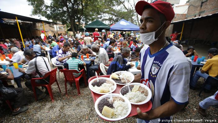 An aid worker helps feed Venezuelan migrants (picture-alliance/AP Photo/F. Vergara)