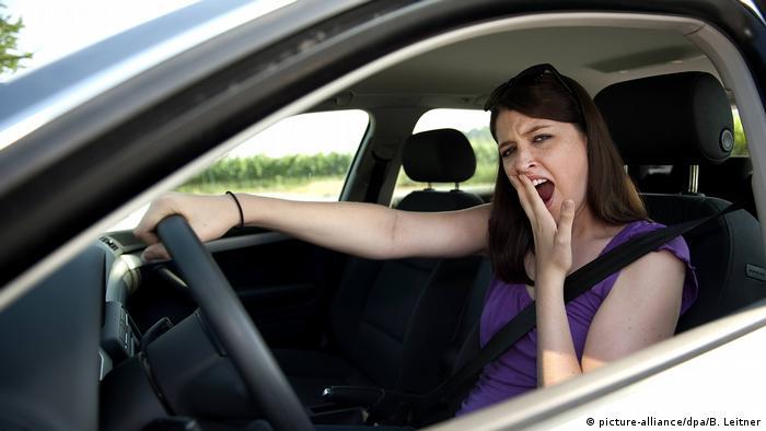 Девушка зевает за рулем