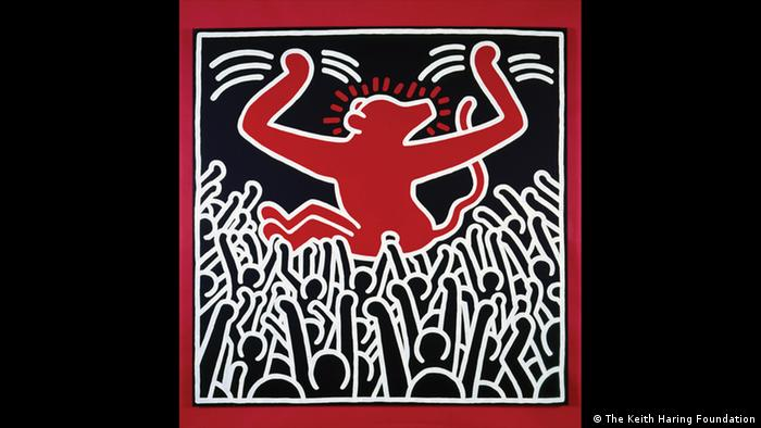 A red monkey being propped by a crowd of people (The Keith Haring Foundation)