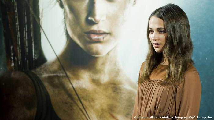 Alicia Vikander in front of a Tomb Raider poster