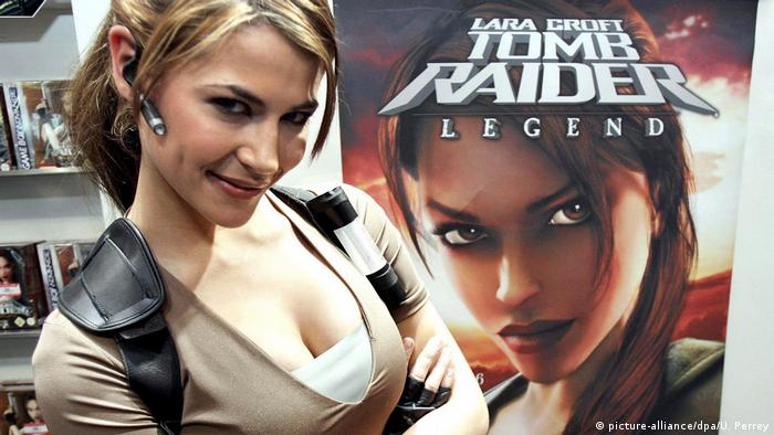 Model Karima Adebibe in front of a poster for the Tomb Raider Legend game.