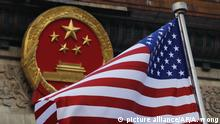 An American flag is flown next to the Chinese national emblem during a welcome ceremony for visiting U.S. President Donald Trump