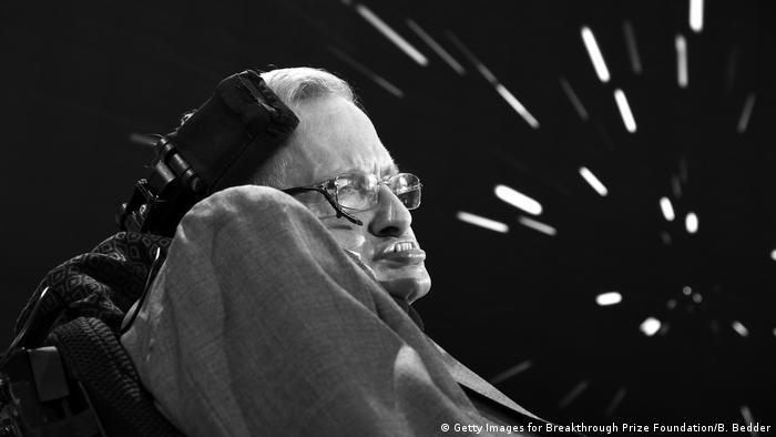 British astrophysicist Stephen Hawking against a black space-like background