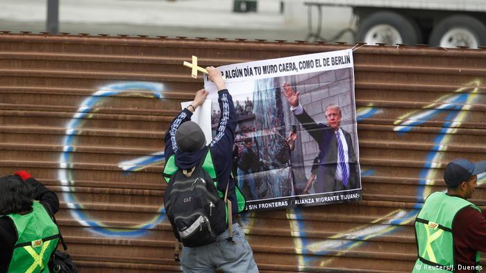 Manifestante pendura cartaz na fronteira do México com os EUA com os dizeres um dia seu muro cairá, como o de Berlim