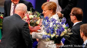 Меркель принимает букеты цветов