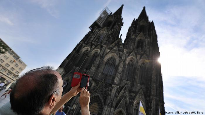 Tourist takes a photo of the Cologne Cathedral with his smartphone (picture-alliance/dpa/O. Berg)