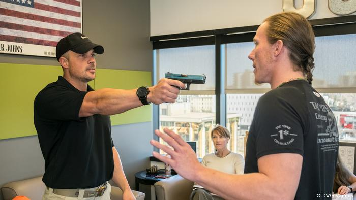 Trainer Joe Green explains how you grab a gun when it's pointed at you during a course to learn how to behave if threatened by a shooter, in Denver, Colorado