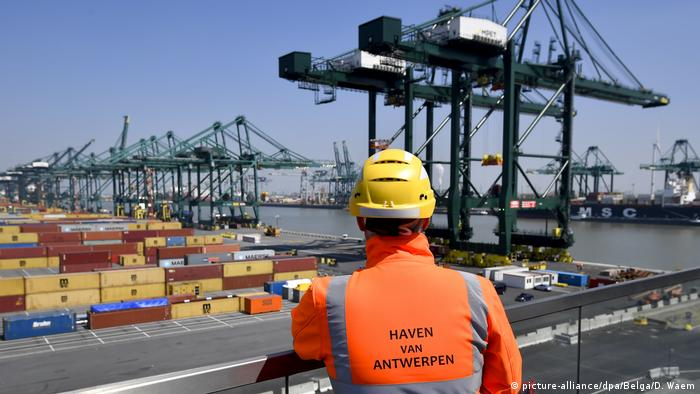 Photo: A Antwerp port employee looks at containers and cranes (Source: picture-alliance/dpa/Belga/D. Waem)